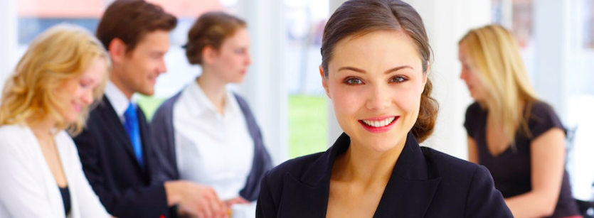 business woman in forground smiling while team works together behind her. Leadership Coaching and development page