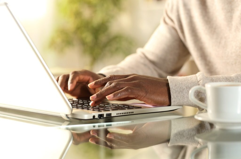 person typing at a laptop researching target companies for job search
